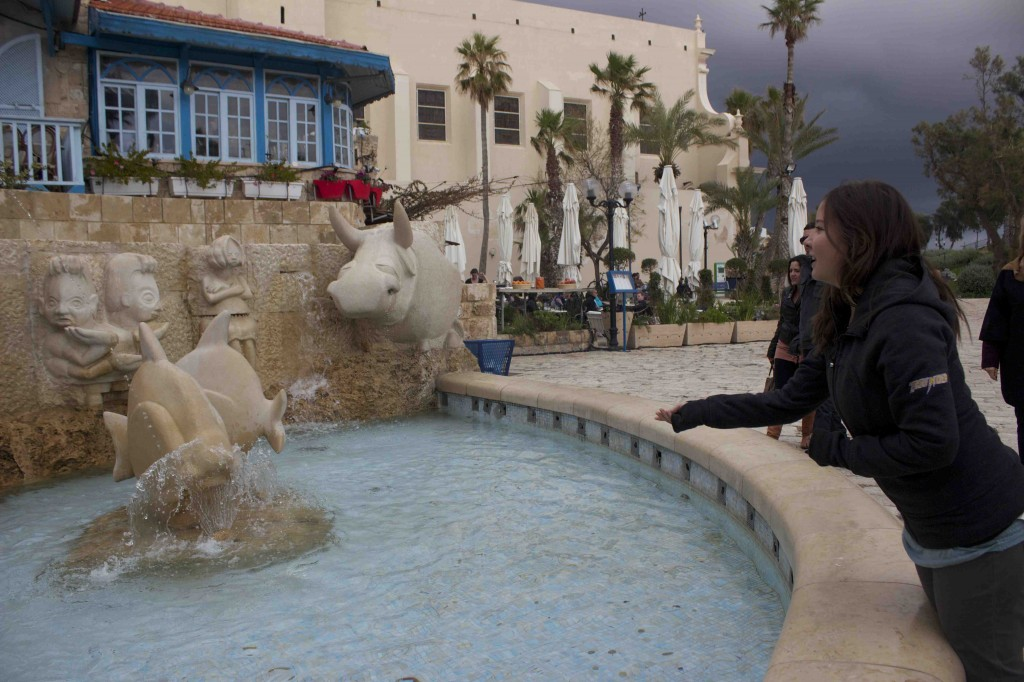 Siobhan tossing a coin at the zodiac fountain.