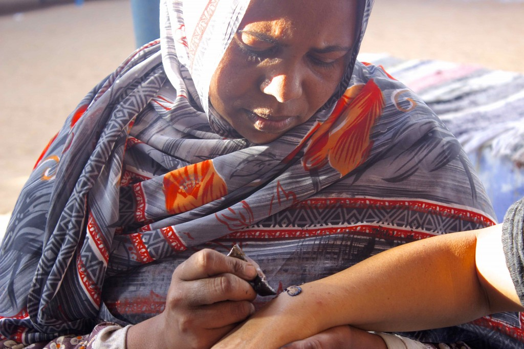A nubian woman making a tattoo with henna on Wanda.