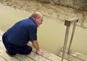 Seamus dipping his fingers in the water where Jesus was baptized.