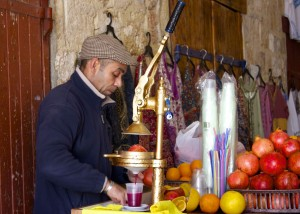 A man making fresh pomegranate juice.