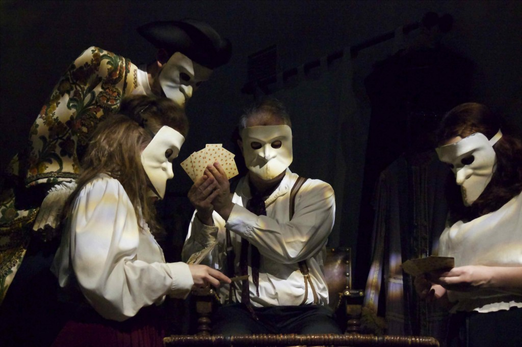 The actors wearing the Bauta masks while gambling.