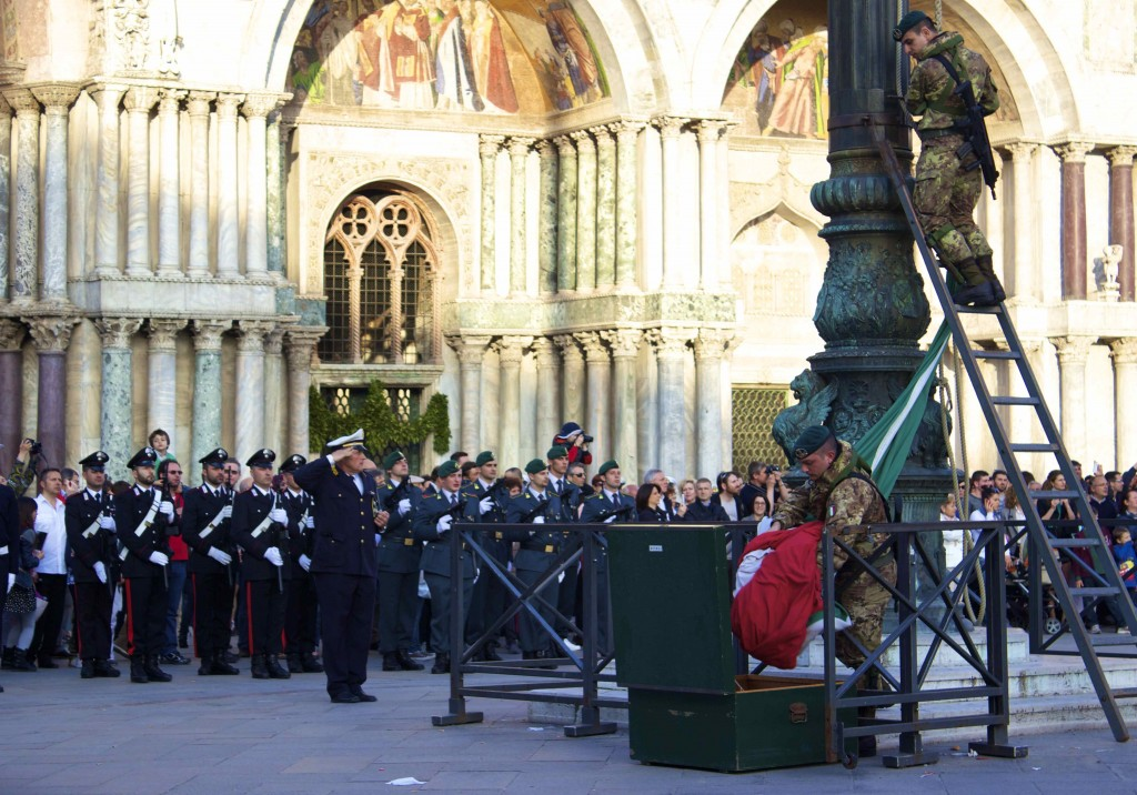 The forces of Italy taking down the Italian flag in front of the Basilica of Saint Mark.