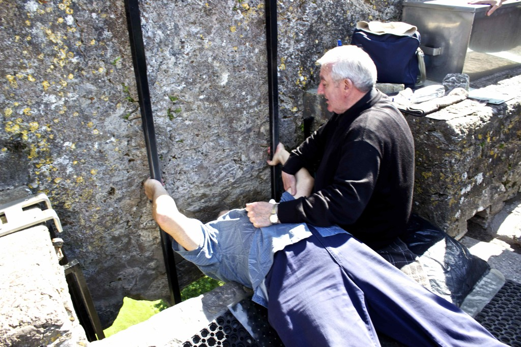 Seamus kissing the Blarney stone with the helping hand of the assistant.